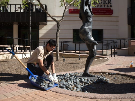 Adam Villanueva removes landscaping rock Aug. 21, 2017, from in front of the Herberger Theater Center in Phoenix ahead of President Donald Trump's rally at the Phoenix Convention Center Aug. 22.