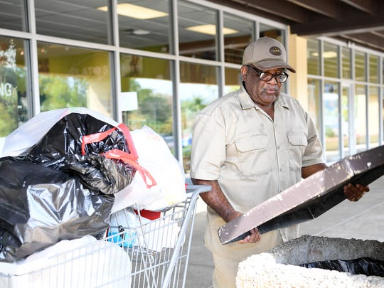 Paul Poore empties a trash can at the Westgate Shopping Center on Wednesday, Aug. 30, 2017.