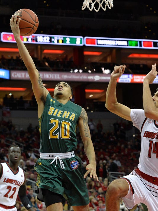Siena guard Roman Penn (20) goes in for a layup ahead of the defense of Louisville forward Anas Mahmoud (14) during the first half of an NCAA college basketball game, Wednesday, Dec. 6, 2017, in Louisville, Ky. (AP Photo/Timothy D. Easley)