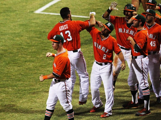 Miami's Willie Abreu (13) celebrates with his teammates after scoring during an NCAA college regional baseball game against Long Beach State, Sunday, June 5, 2016, in Coral Gables, Fla. (Logan Riely/The Miami Herald via AP)  MAGS OUT; MANDATORY CREDIT