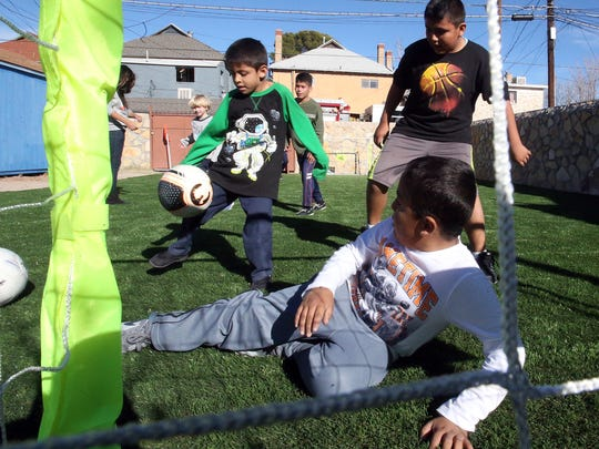 Oliver Elias, bottom, plays soccer with other children on their newly installed synthetic turf backyard soccer field at La Posada Home at 1020 N. Campbell Monday.