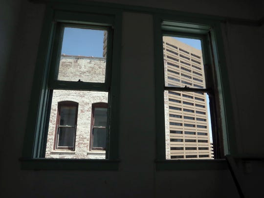 Old wood-framed windows provide views of nearby Downtown