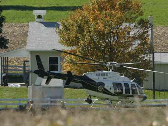 A police helicopter takes off from the scene of a school shooting in Nickel Mines, Pa., Monday, Oct. 2, 2006. An armed man walked into an Amish school, sent the boys outside and tied up and shot the girls, killing four of them, authorities said. The gunman, Charles Carl Roberts IV, 32, a truck driver from the town of Bart, apparently killed himself, state police Commissioner Jeffrey B. Miller said. Four children were found dead at the scene and seven others were taken to hospitals, where another girl later died from her injuries.