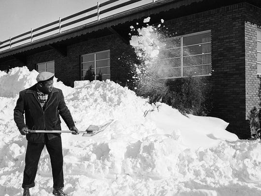 FILE - In this Feb. 7, 1961 file photo, World Heavyweight champion Floyd Patterson takes time from his usual training routine as he shovels snow at his Spring Valley, N.Y. training camp. More than 20 inches fell in the New York City region, with up to 40 inches in the central part of the state and lesser but still substantial amounts of more than a foot throughout New England. (AP Photo/File)