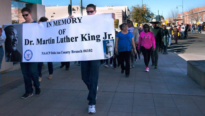 Members of the public join together for a peace march along Main Street on Sunday in honor of Dr. Martin Luther King Jr. Monday is a national holiday in honor of the slain civil rights leader.