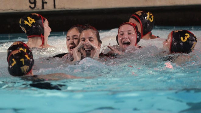 Palm Desert High School's girls celebrate with their coach their win of La Quinta High School at La Quinta.