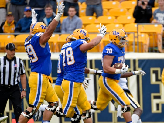 (From left) Pittsburgh's Adam Bisnowaty and Alex Bookser celebrate as offensive lineman Brian O'Neill  scores a touchdown during the first half Saturday.