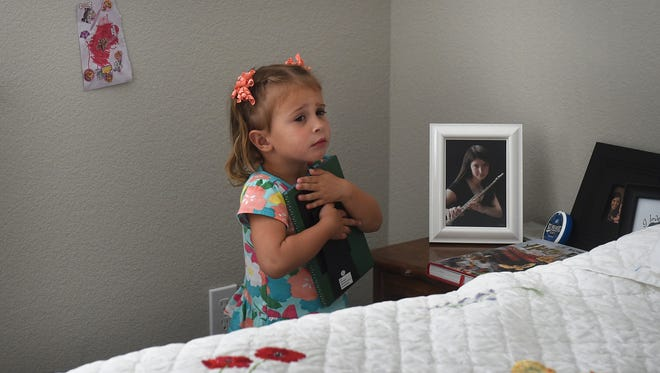 3-year-old Emmeline Orton hugs a framed photo of her mother in her bedroom in Reno on Sept. 2, 2017. A year ago OrtonÕs mother Alisa Hardy Orton was killed by a drunk driver near her home in Sommersett.  Jason Bean/Reno Gazette-Journal- USA TODAY NETWORK