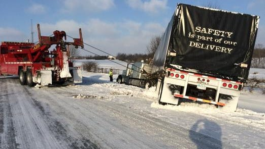 Commercial vehicles get a tow after sliding off of U.S. 30 east of Mansfield this morning.