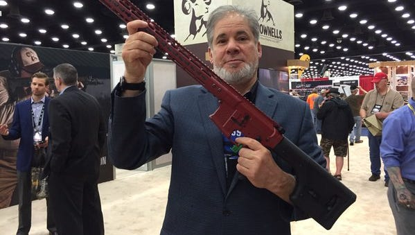 The CJ's Andrew Wolfson shows an AR-15 assault rifle up for raffle at NRA annual meeting.