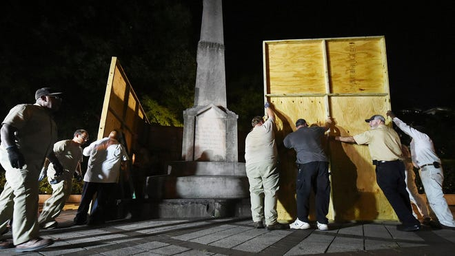 City workers use plywood panels to cover the Confederate Monument in Linn Park in Birmingham, Ala., in 2017.