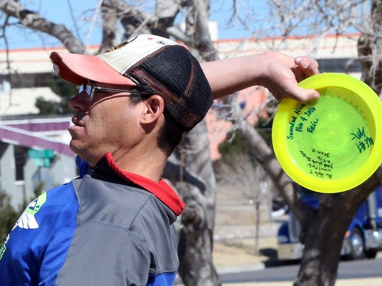 Chris Alexander prepares to fling a disc toward the goal during a disc golf game. Overhead throws carry the disc a longer distance.