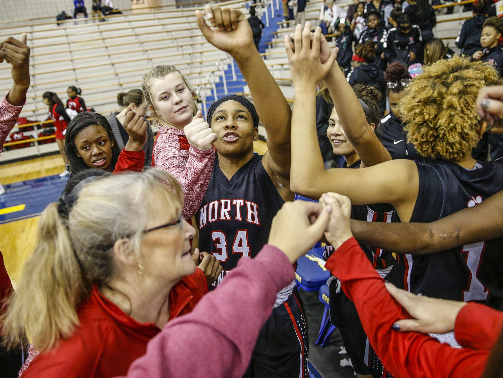 """North Central Panthers' Ajanae« Thomas (34) breaks a huddle with her team before the Panthers' game against the Carmel Greyhounds at Carmel High School on Friday, Dec. 16, 2016. Thomas wears the number 34 in honor of her late mother Nicole who was known as """"Lady Barkley,"""" after Charles Barkley, in the Detroit area."""