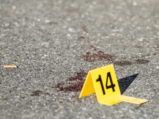 Blood is marked by an evidence marker as police investigate a shooting that occurred at the intersection of Ninth and Mifflin streets around 4:30 p.m. on Wednesday, August 16, 2017. The shooting sent one woman to the hospital.