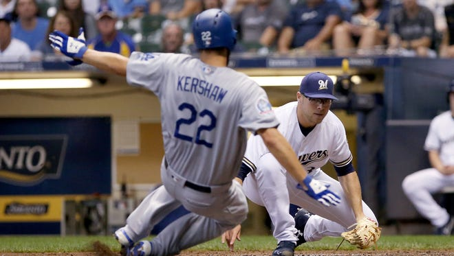 Brewers reliever Corbin Burnes waits to tag Clayton Kershaw of the Dodgers, who was trying to score after a pitcher squirted away from catcher Erik Kratz in the fifth inning Saturday night. Burnes picked up his first major-league victory in the game.