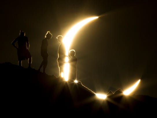Hikers watch a partial solar eclipse from Papago Park