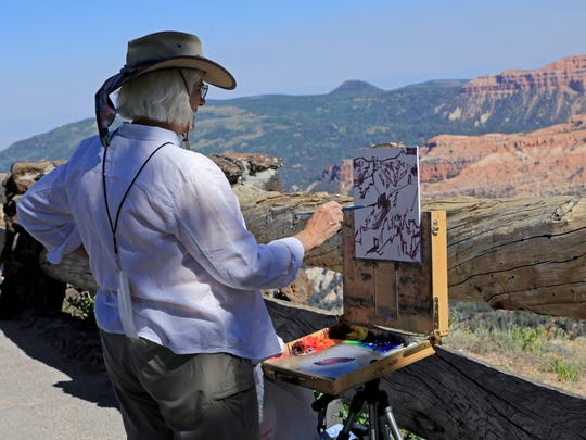 "Rachel Pettit demonstrates plein air painting techniques Monday at Cedar Breaks National Monument for the ""Chasing Light"" plein air event."