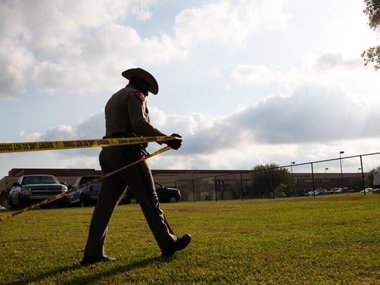 A Texas Department of Public Safety officer places crime scene tape across Santa Fe High School on May 19, 2018, the day after a shooting a mass shooting in Santa Fe, Texas.