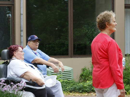 Margrit Moan-Nachreiner, right, and residents Joy Atchison and James Morrison call the cats during feeding time on Tuesday, June 12, 2018, at Mount View Care Center in Wausau.