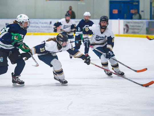 Essex's Abigail Robbins, center, reaches for the puck