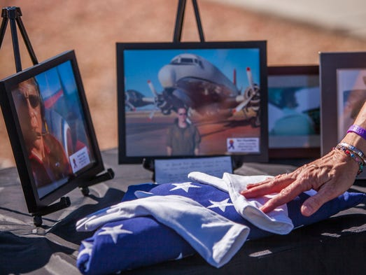 A folded flag sits on a table next to photos of Todd