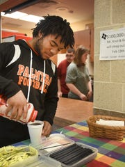 Alon Rhett adds cream and sugar to his coffee ordered at the Palmyra  Area High School Life Skills coffee shop recently. The coffee shop, which is open only on Friday mornings, serves both faculty and students