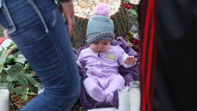 Aeralinn, 6 month old baby sister to Sydney Nikole Alcorn who was killed in a car accident on Monday night, is brought to the memorial for Sydney and the four others killed in the crash on Tuesday, April 11, 2017, in Mason City.