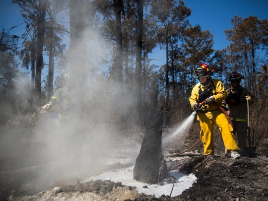 Wild land fire fighters from the Florida Forest Service spray hot spots near the damaged properties on Le Buffs Road on Friday, March 10, 2017. As of 7:30 p.m. Friday, the fire was 65 percent contained on 7,500 acres, state forestry officials said.