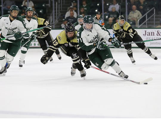MSU's Logan Lambdin chases the puck during the Spartans' 6-4 win over Western Michigan Friday night at Munn Ice Arena.
