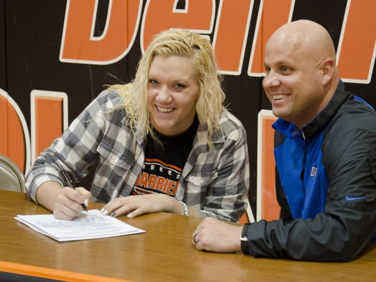 Mikaela Stofferahn of Dell Rapids, left, signs her national letter of intent Thursday, March 24, to attend Dakota Wesleyan University and play basketball for coach Jason Christensen, right.