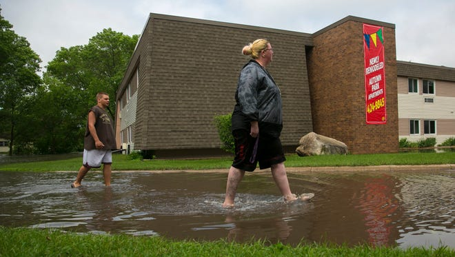 Nicole White and Jordan Holmes wade through the flood waters surrounding Autumn Park Apartments, where White's mother-in-law, Jan Stigers, is a resident, Friday, June 8, 2018 in Mason City, Iowa. Police in the northern Iowa's Mason City say two apartment complexes near an overflowing creek have been evacuated.