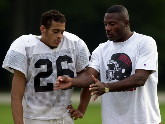 FILE – Indiana Firebirds wide receiver Eddie Brown helps coach defensive back Bobby James of the North Central High School football team in 2001.