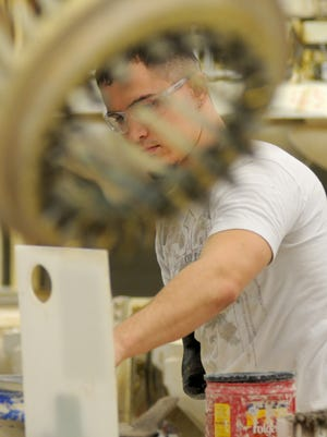 Travis Stone of Lucas works on the line Tuesday morning at Mansfield Plumbing in Perrysville.