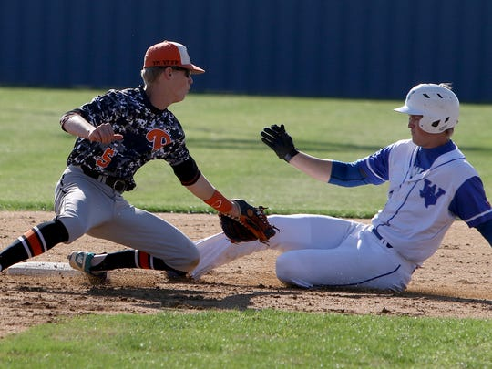 Windthorst's Brady Tackett slides safe into second while tagged by Petrolia's Bailey Sternadel Monday, March 20, 2017, in Windthorst. The Trojans defeated the Pirates 1-0.