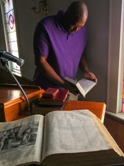 Minister Edgar Scott looks at a Holy Bible near one from 1891 in a fellowship, which was santuary in 1992, at Generostee Baptist Church in Starr.