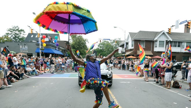 """Carlos Merriweather, who labels himself """"Rochester's Social Butterfly,"""" gets the attention of the crowd  at the intersection of Park Avenue and Berkeley Street during the Pride Parade on Saturday."""
