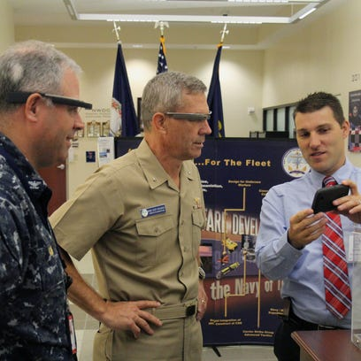 Dr. Josh Kvavle,  right, from Space and Naval Warfare Systems Command, Center Pacific, demonstrates potential uses of Google Glass to Rear Adm. Scott Stearney, center, commander of Navy Warfare Development Command, and his chief of staff, Capt. Thomas Kiss, at the Navy Warfare Development Command headquarters at Naval Station Norfolk. The demonstration project is developed by the chief of naval operations' Rapid Innovation Cell program, which uses commercial technologies to rapidly prototype solutions for the fleet. (U.S. Navy photo by Joseph Bara/Released)