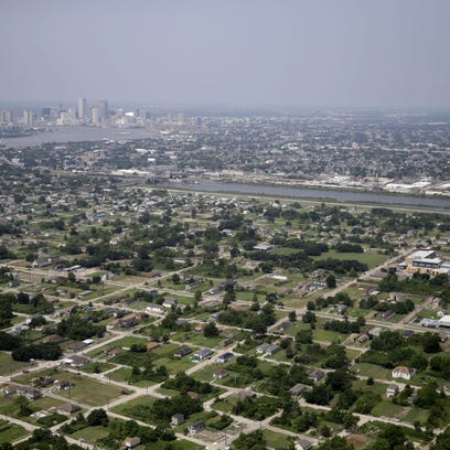 This July 29, 2015, aerial photo shows empty lots and mostly new buildings in the Lower 9th Ward section of New Orleans, foreground. Ten years after Katrina, New Orleans remains a work in progress, aiming to reverse historic racial and economic injustices.