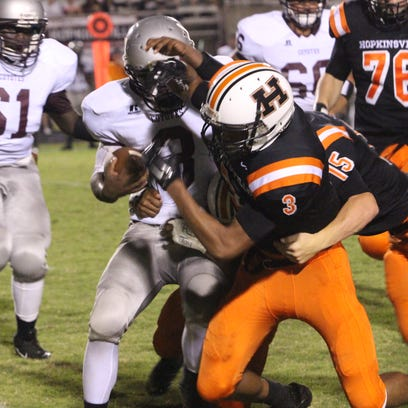 Hopkinsville's Vincent Brown (34) tries to elude the tackle of West Creek's Tyler Moore during the first half of their game Saturday at the Stadium of Champions.