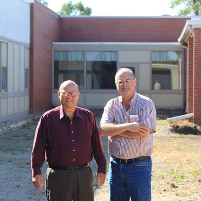 Tony Caccomo, left, and Jim Milano stand in front of a former school building their company, National Foodworks Services, plans to convert into a food-processing center.  Both are former Poughkeepsie businessmen.