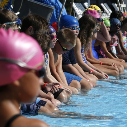 Children line the edges of the pool at the Trousdell Aquatics Center during a swimming lesson.