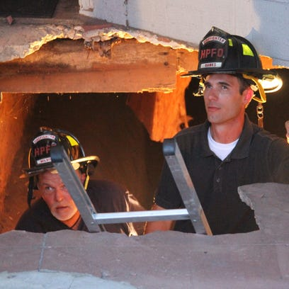 Honea Path firefighters work in a hole after part of a sidewalk collapsed in downtown Monday evening.