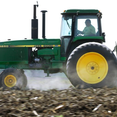 FILE - In this April 2, 2012 file photo, Derek Long uses a John Deere tractor to disk and cultivate a field in preparation for planting corn in Loami, Ill. Deere & Co. reports quarterly earnings on Wednesday, Feb. 12, 2014. (AP Photo/Seth Perlman, File)