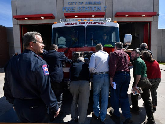 Abilene Fire Department Chief Larry Bell, left, walks behind a group of former and current Abilene City Council members and citizens as they ceremoniously push a fire engine into the new Station 7 on March 9. During the station's dedication, Bell announced he will retire May 31.