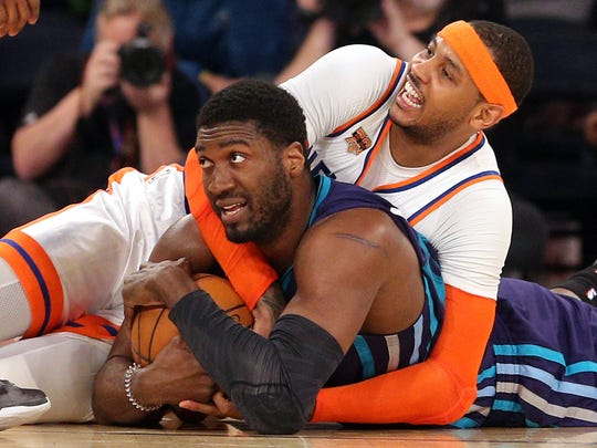 Knicks small forward Carmelo Anthony, background, and Charlotte Hornets center Roy Hibbert fight for a loose ball on Friday night at Madison Square Garden. Anthony scored 18 points as the Knicks won, 110-107.