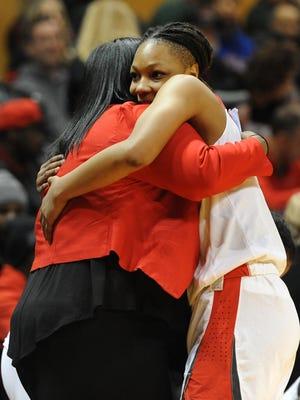 Detroit Edison guard Gabrielle Elliott (3) hugs head coach Monique Brown near the end of the fourth quarter Saturday.
