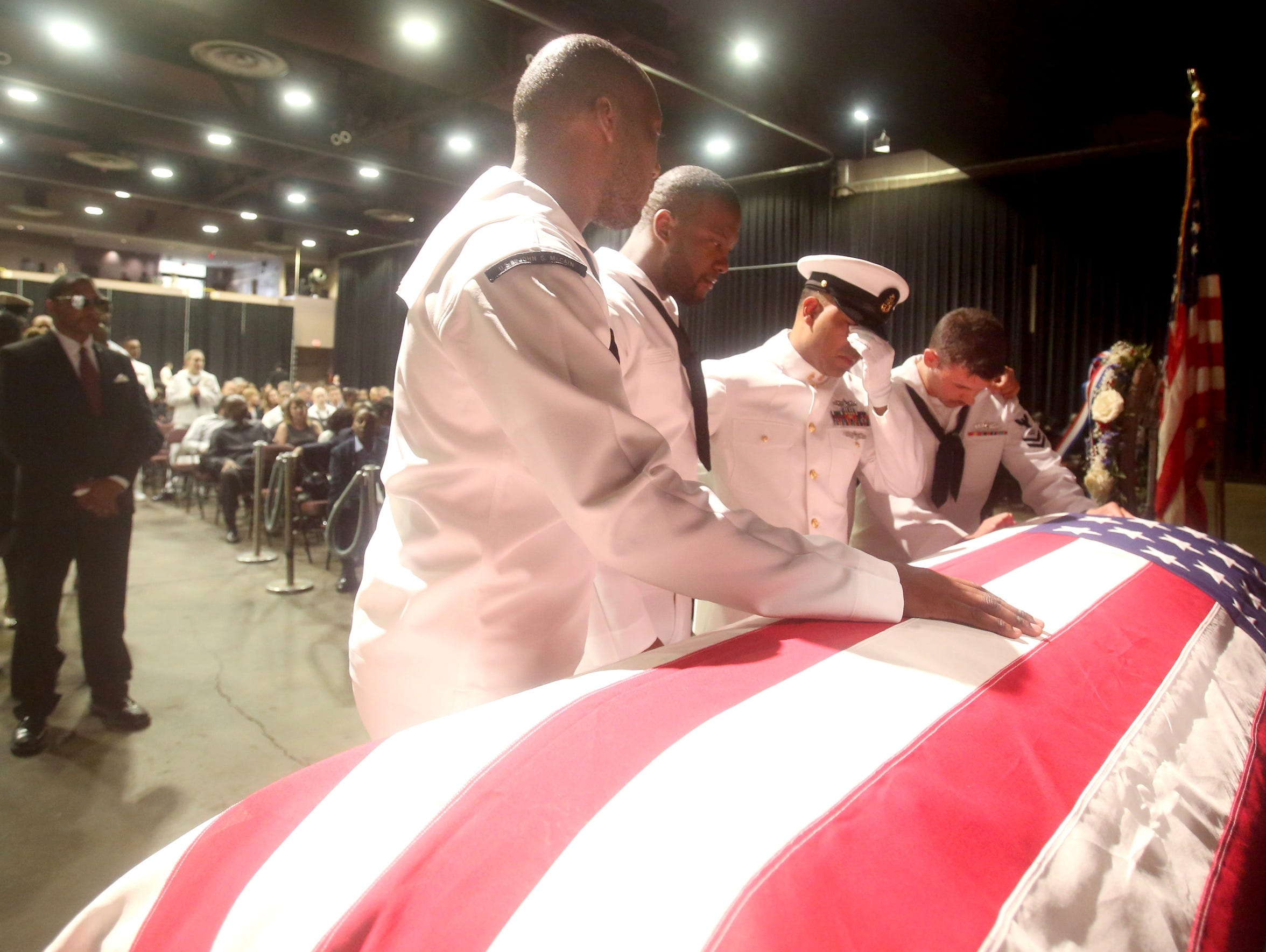 Members of the United States Navy stand over the casket