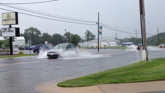 Heavy rain floods NE Front Street in Milford on Thursday afternoon.
