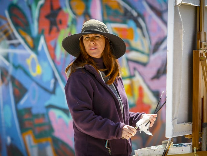 Valeri Larko of New Rochelle, works on a street scene in a small industrial section on Boone Avenue in the South Bronx.  April 20, 2014.