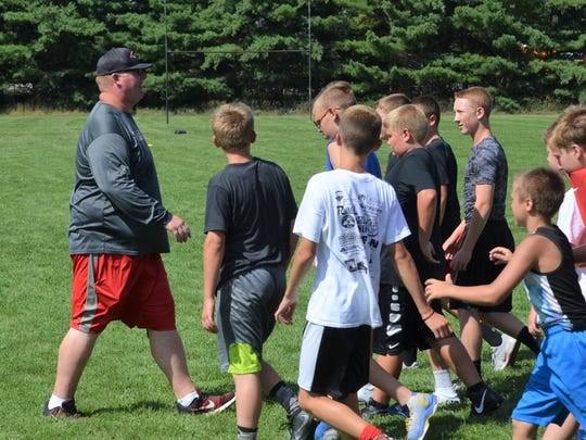 Marshall head coach  Jason Stealy works with players at a youth camp earlier this summer.